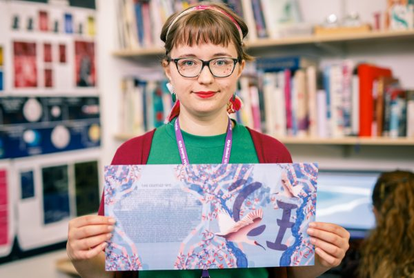 graphic design student holding her art work