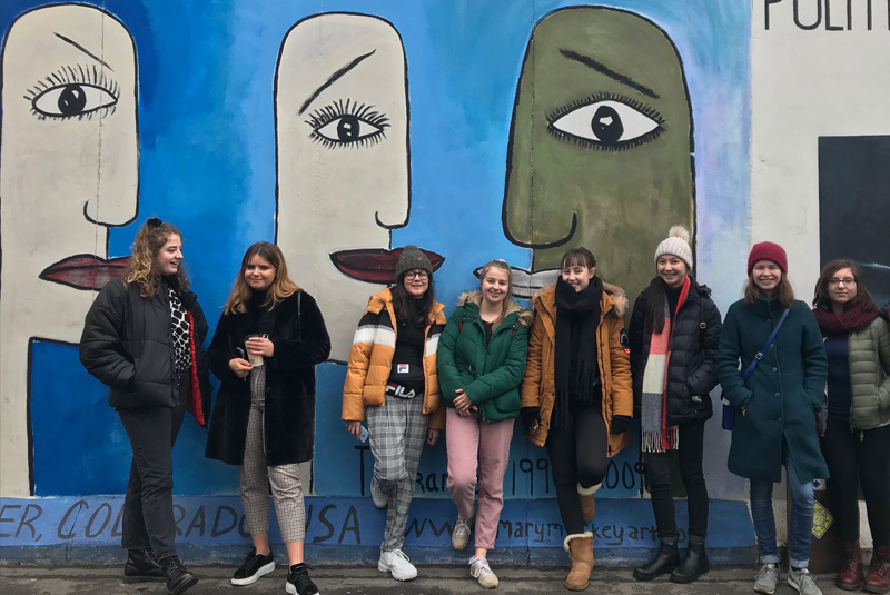 students standing in front of the remains of the Berlin Wall